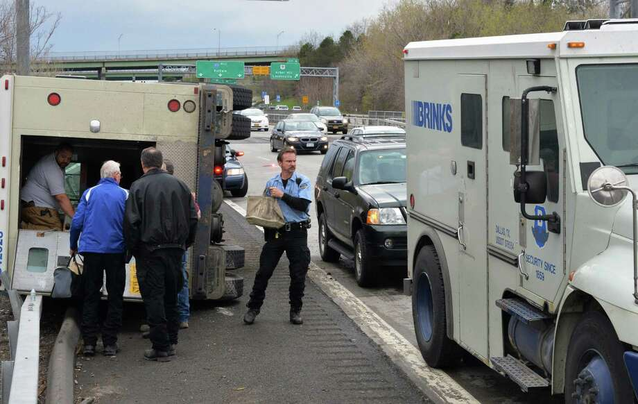 Brinks guards transfer cargo from an overturned armored truck, left, after an accident at exit 6A of I90 Saturday May 3, 2014, in Albany, NY.  (John Carl D'Annibale / Times Union) Photo: John Carl D'Annibale