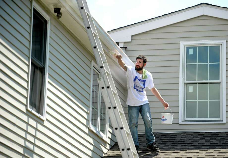 Nick Sicignano, of Seymour, a volunteer from Church of the Good Shepherd, paints the trim on Karen Wildman's Shelton home Saturday, May 3, 2014, during the 27th annual HomeFront day where volunteers team up to bring home repair relief to low income families. Photo: Autumn Driscoll / Connecticut Post
