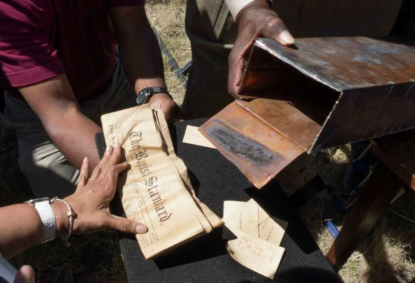 The contents of a time capsule found in the burned remains of the old Childress Memorial Church of God in Christ in Dignowity Hill are poured out after it was opened during the groundbreaking ceremony for the church's new location on Binz-Engelman Road on Saturday, May 3, 2014.