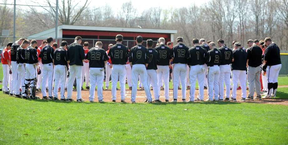 Jonathan Law and Foran baseball players take a moment of silence before their game Saturday, May 3, 2014, at Foran High School in Milford, Conn., to honor slain Law student Maren Sanchez. Photo: Autumn Driscoll / Connecticut Post