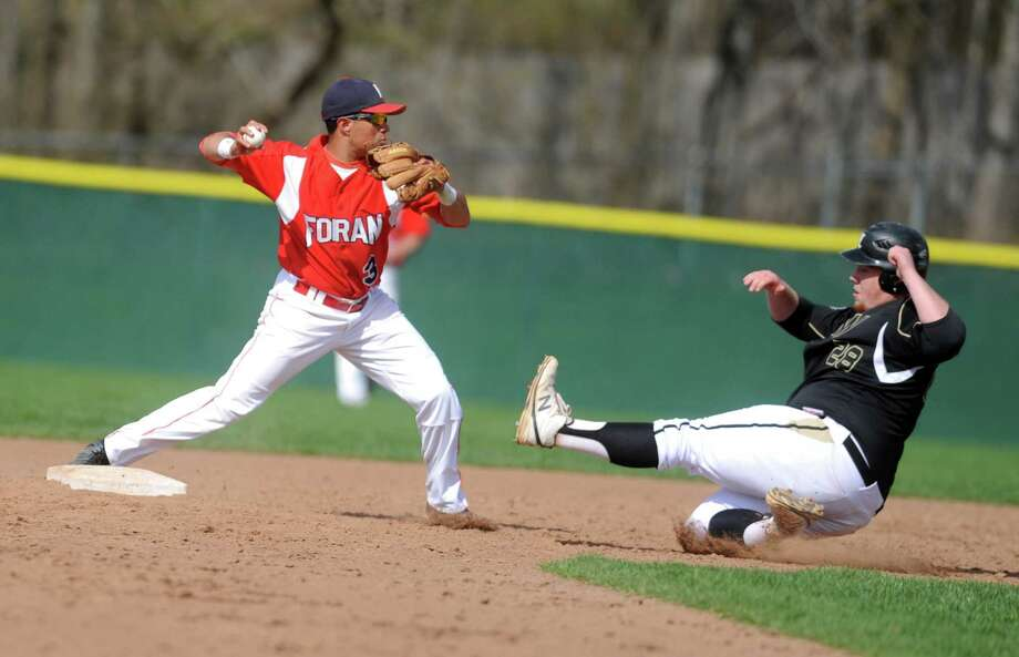 Foran's Reinaldo Jackson throws to first as Jonathan Law's Kevin Johnson slides to second during their game Saturday, May 3, 2014, at Foran High School in Milford, Conn. Photo: Autumn Driscoll / Connecticut Post