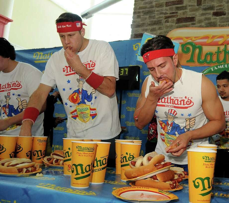 "Erik ""The Red"" Denmark and Juan ""More Bite"" Rodriguez compete at the Nathan's Famous Hot Dog Eating Contest regional qualifier at Memorial City Mall Saturday May 03, 2014.(Dave Rossman photo) Photo: Dave Rossman, For The Houston Chronicle / © 2014 Dave Rossman"