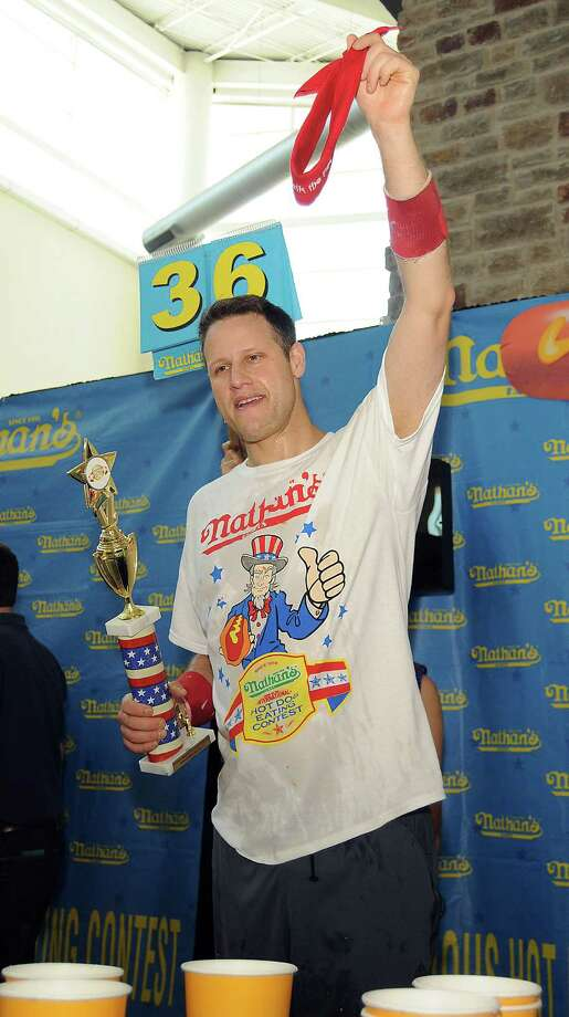 "Erik ""The Red"" Denmark holds his trophy after winning the mens division at the Nathan's Famous Hot Dog Eating Contest regional qualifier at Memorial City Mall Saturday May 03, 2014. Denmark ate 36 hot dogs to take the title.(Dave Rossman photo) Photo: Dave Rossman, For The Houston Chronicle / © 2014 Dave Rossman"