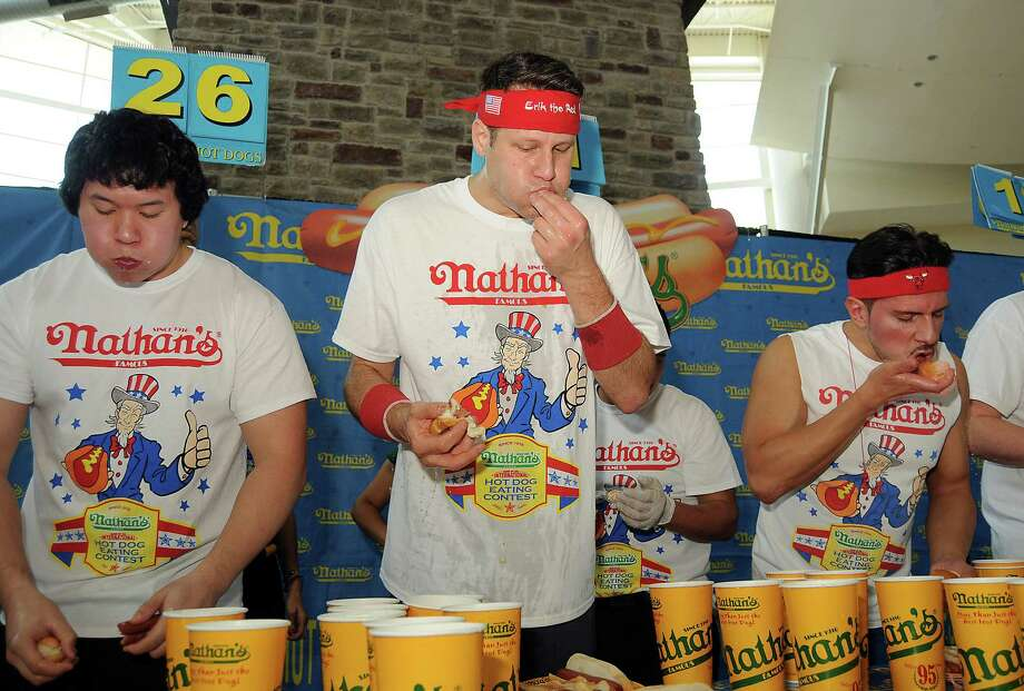 "From left: Jimmy Chi, Erik ""The Red"" Denmark and Juan ""More Bite"" Rodriguez compete at the Nathan's Famous Hot Dog Eating Contest regional qualifier at Memorial City Mall Saturday May 03, 2014.(Dave Rossman photo) Photo: Dave Rossman, For The Houston Chronicle / © 2014 Dave Rossman"
