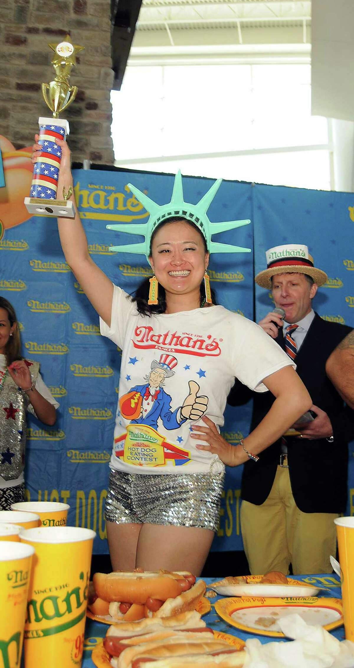 Mary Bowers holds her trophy after winning the female category at the Nathan's Famous Hot Dog Eating Contest regional qualifier at Memorial City Mall Saturday May 03, 2014. Bowers ate 11 3/4 hot dogs to win the title.(Dave Rossman photo)