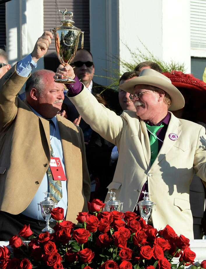 Perry Martin, left and Steve Coburn co-owners raise the winner's trophy aloft after winning the 140th running of The Kentucky Derby with their horse California Chrome Saturday evening May 3, 2014 in Louisville, Kentucky  (Skip Dickstein / Times Union) ORG XMIT: J=0504_derby Photo: SKIP DICKSTEIN