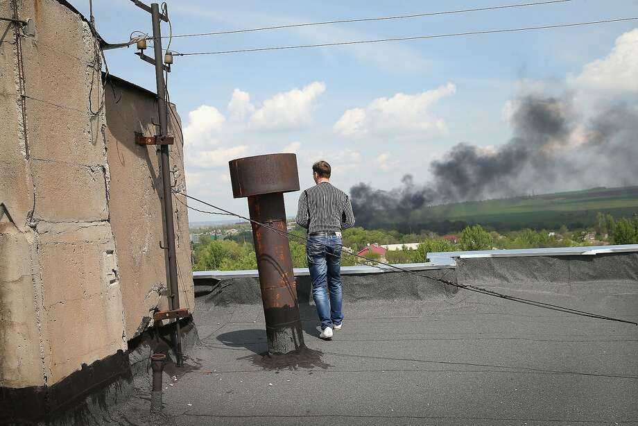 KRAMATOVSK, UKRAINE - MAY 03:  A man watches from a rooftop as Ukrainian soldiers assault a pro-Russian activists roadblock on May 3, 2014 in Kramatovsk, Ukraine. At least one person was reported killed in the fight. Over the past couple of days the Ukrainian army has been assaulting pro-Russian checkpoints in and around Kramatovsk which sits on the edge of Slovyansk, a pro-Russian activist stronghold.  (Photo by Scott Olson/Getty Images) *** BESTPIX *** Photo: Scott Olson, Getty Images
