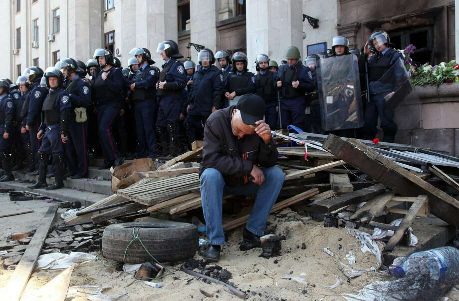 """TOPSHOTS A Pro-Russian activist sits in front of policemen guarding the burned trade union building in the southern Ukrainian city of Odessa on May 3, 2014. More than 30 people were killed in a """"criminal"""" blaze in Ukraine's southern city of Odessa, as violence spread across the country during the bloodiest day since Kiev's Western-backed government took power. Ukraine's interior ministry said at least 31 people had died in the fire Friday, with local media reporting that pro-Russian militants were believed to have been in the burning building at the time.  AFP PHOTO/ ANATOLII STEPANOVANATOLII STEPANOV/AFP/Getty Images Photo: Anatolii Stepanov, AFP/Getty Images"""