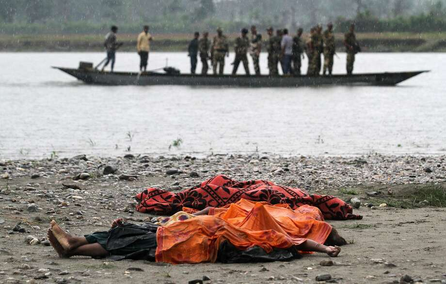 EDS NOTE GRAPHIC CONTENT - Bodies of victims killed in ethnic violence lie covered in the rain on the banks of the River Beki, as security officers patrol the area on a boat at Khagrabari village, in the northeastern Indian state of Assam, Saturday, May 3 2014. Police in India arrested 22 people after separatist rebels went on a rampage, burning homes and killing dozens of Muslims in the worst outbreak of ethnic violence in the remote northeastern region in two years, officials said Saturday. (AP Photo/Anupam Nath) Photo: Anupam Nath, Associated Press