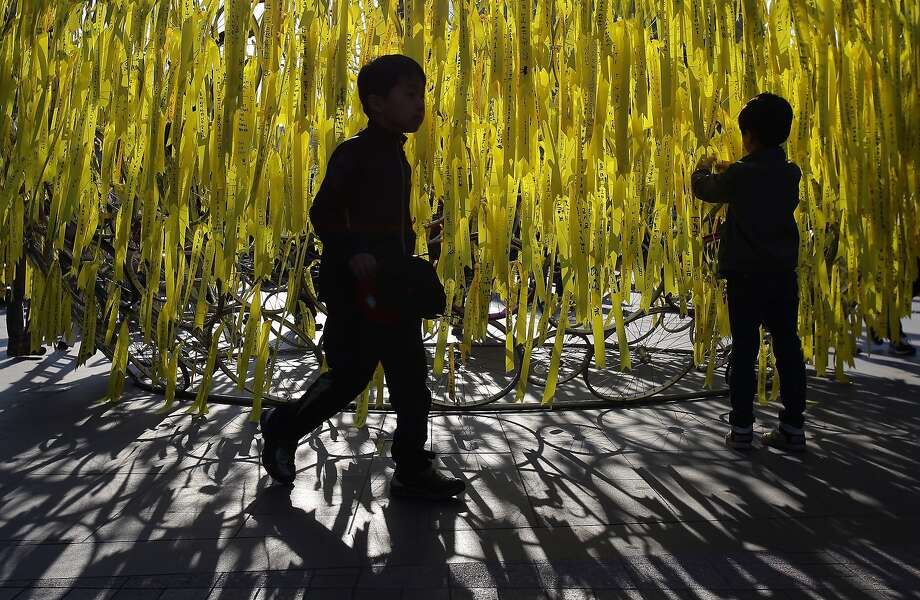 A tribute to the dead: In Seoul, a boy ties a yellow ribbon for the safe return of 
