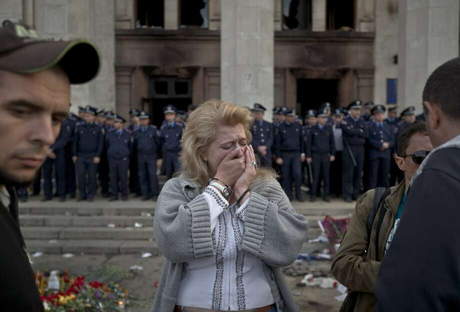 A woman cries back dropped by police troops guarding the burnt trade union building in Odessa, Ukraine, Saturday, May 3, 2014, where more than 30 people died trying to escape during clashes the day before. Odessa had been largely tranquil since the February toppling of President Viktor Yanukovych, who fled to Russia. But clashes erupted Friday between pro-Russians and government supporters in the key port on the Black Sea coast, located 550 kilometers (330 miles) from the turmoil in the east. (AP Photo/Vadim Ghirda) Photo: Vadim Ghirda, Associated Press