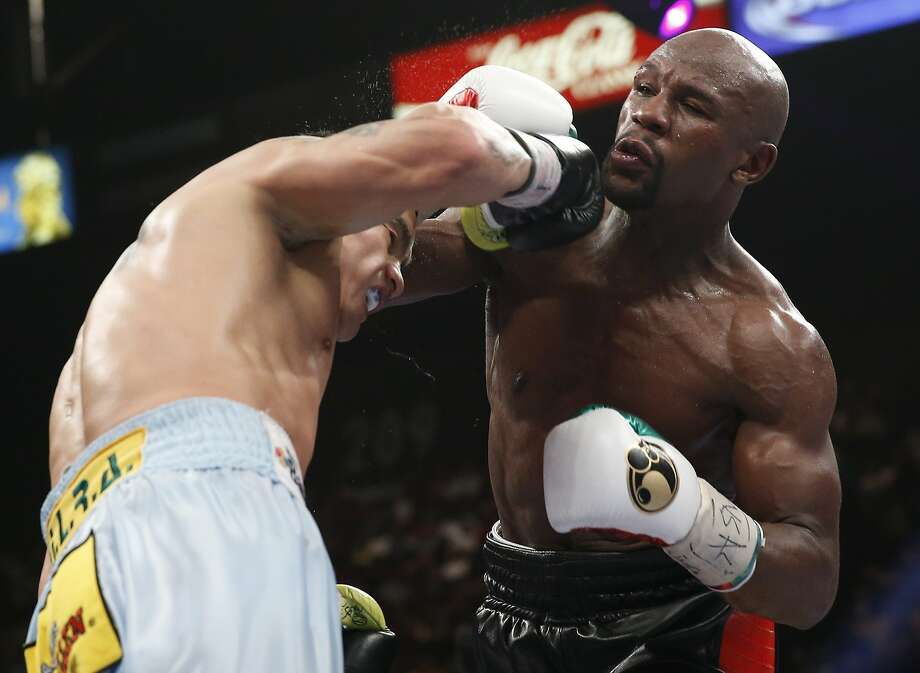 Floyd Mayweather Jr. (right) trades punches with Marcos Maidana in their WBC-WBA welterweight title fight. Photo: Eric Jamison, Associated Press