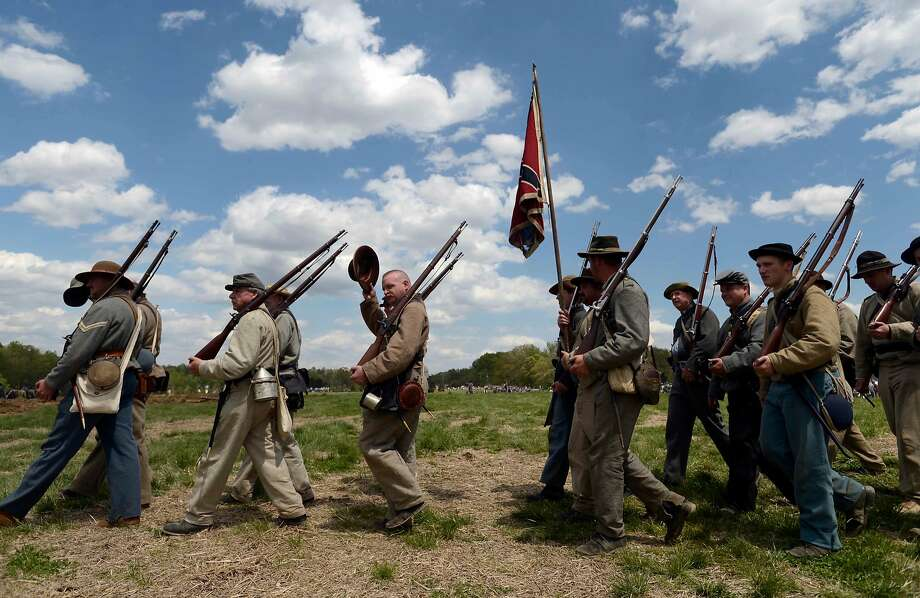 Confederate troops march back to camp after fighting in a re-enactment of the Battle of the Wilderness, southwest of Fredricksburg, Va. on Saturday, May 3, 2014. Re-enactors and spectators converged on Spotsylvania Courthouse to commemorate the 150th anniversary of the Civil War battle. (AP Photo/The Free Lance-Star, Reza Marvasthi) Photo: Reza A. Marvashti, Associated Press