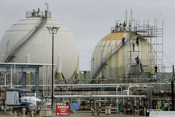 Employees work on a storage tank inside the Chevron Corp. Richmond Refinery stands in Richmond, California, U.S., on Thursday, April 24, 2014. Chevron Corp. hopes to gain city approval to finish hydrogen plant at the Richmond refinery in June or July. Photographer: David Paul Morris/Bloomberg