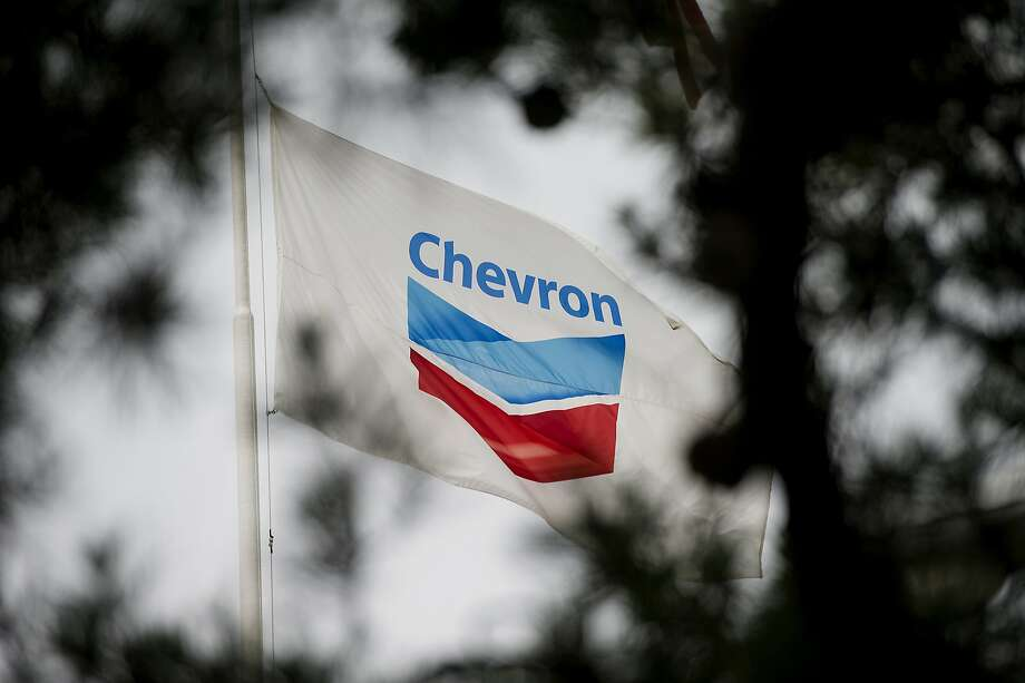 The Chevron Corp. flag flies in front of the company's administrative building inside the Chevron Corp. Richmond Refinery stands in Richmond, California, U.S., on Thursday, April 24, 2014. Chevron Corp. hopes to gain city approval to finish hydrogen plant at the Richmond refinery in June or July. Photographer: David Paul Morris/Bloomberg Photo: David Paul Morris, Bloomberg