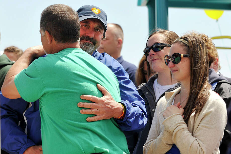 Jesse Lewis' father Neil Heslin, in blue, hugs Carlos Soto, Victoria Soto's father, as Carlos' daughter, Carlee, looks on during the Sandy Ground Project: Where Angels Play dedication ceremony to honor Sandy Hook Elementary School shooting victim Jesse Lewis at West Beach in Stamford, Conn., on Sunday, May 4, 2014. Photo: Jason Rearick / Stamford Advocate