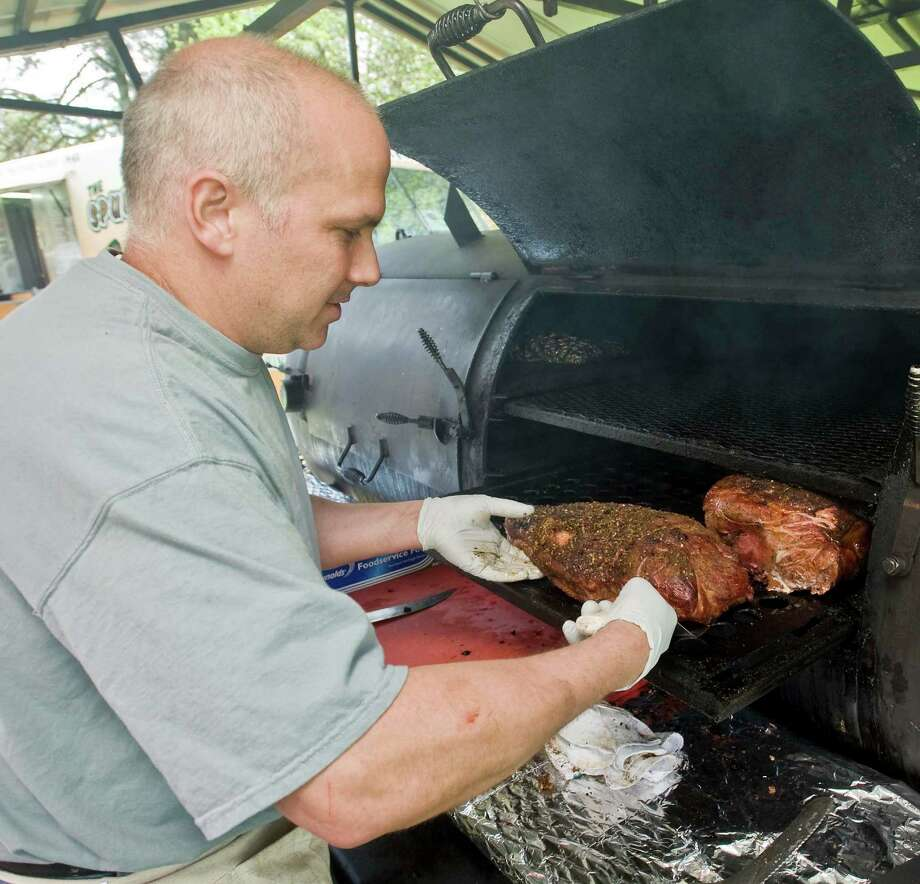 Wire Mill BBQ owner Gino Marsili, of Redding, cooks a beef brisket at the Ridgefield Gone Country Barbecue Festival held at the Ridgefield Community Center. Sunday, May 4, 2014 Photo: Scott Mullin / The News-Times Freelance