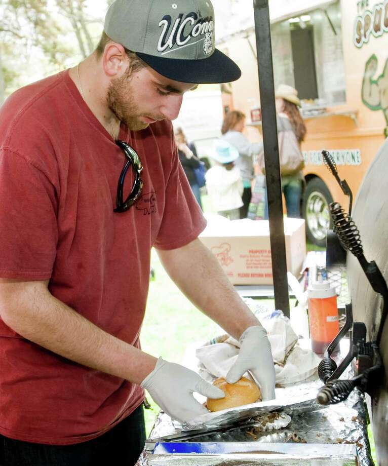 Wire Mill BBQ employee Brendan Veno of Redding wraps a pulled-pork sandwich at the Ridgefield Gone Country Barbecue Festival held at the Ridgefield Community Center. Sunday, May 4, 2014 Photo: Scott Mullin / The News-Times Freelance