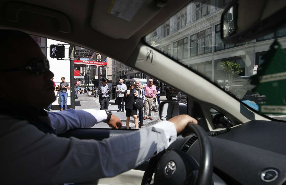 In this file photo, an Uber driver works in San Francisco. An Uber driver in San Francisco hit a pedestrian and three parked cars after having a seizure Saturday night.