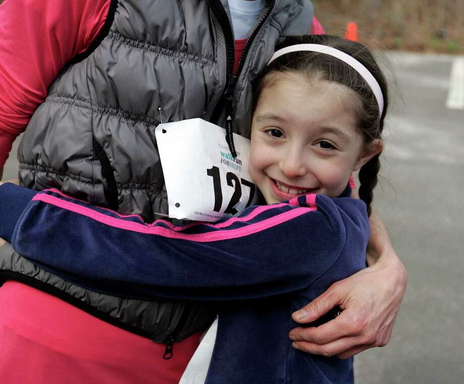 Arriana Netter, 7, of Greenwich hugs her mother after the family completed the 5K run at the annual CancerCare 5K Walk/Run at Tod's Point. Hundreds of runners and walkers competed in the non-profit fundraiser in Greenwich, Conn. on Sunday May 4, 2014 Photo: J. Gregory Raymond / Greenwich Time Freelance;  © J. Gregory Raymond