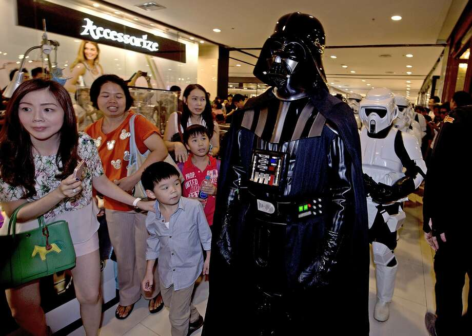"A member (2nd R) of the Star Wars fan club in Thailand, dressed as Darth Vader, parades with others to celebrate ""Star Wars Day"" at a shopping mall in Bangkok on May 4, 2014.  Members of the club dressed up in costume to parade around and raise funds for an orphanage charity. Photo: Pornchai Kittiwongsakul, AFP/Getty Images"