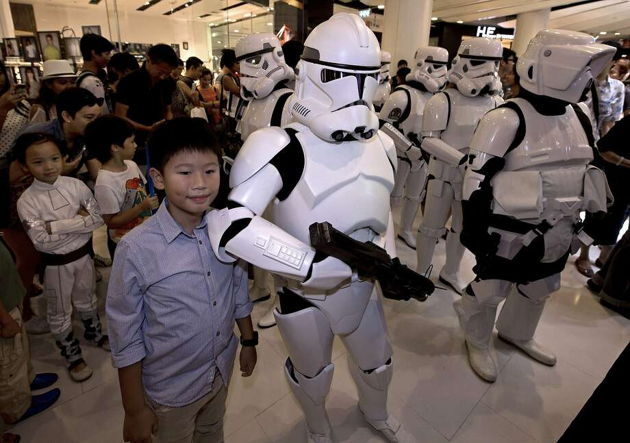 """Thai children pose with members of the Star Wars fan club in Thailand, dressed as Stormtroopers, as they celebrate """"Star Wars Day"""" at a shopping mall in Bangkok on May 4, 2014.  Members of the club dressed up in costume to parade around and raise funds for an orphanage charity. Photo: Pornchai Kittiwongsakul, AFP/Getty Images"""
