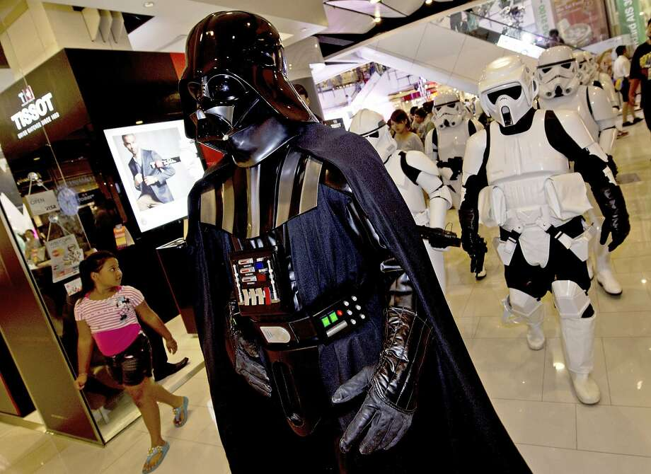 "A member (C) of the Star Wars fan club in Thailand, dressed as Darth Vader, parades with others dressed as Stormtroopers (back R) to celebrate ""Star Wars Day"" at a shopping mall in Bangkok on May 4, 2014.  Members of the club dressed up in costume to parade around and raise funds for an orphanage charity. Photo: Pornchai Kittiwongsakul, AFP/Getty Images"