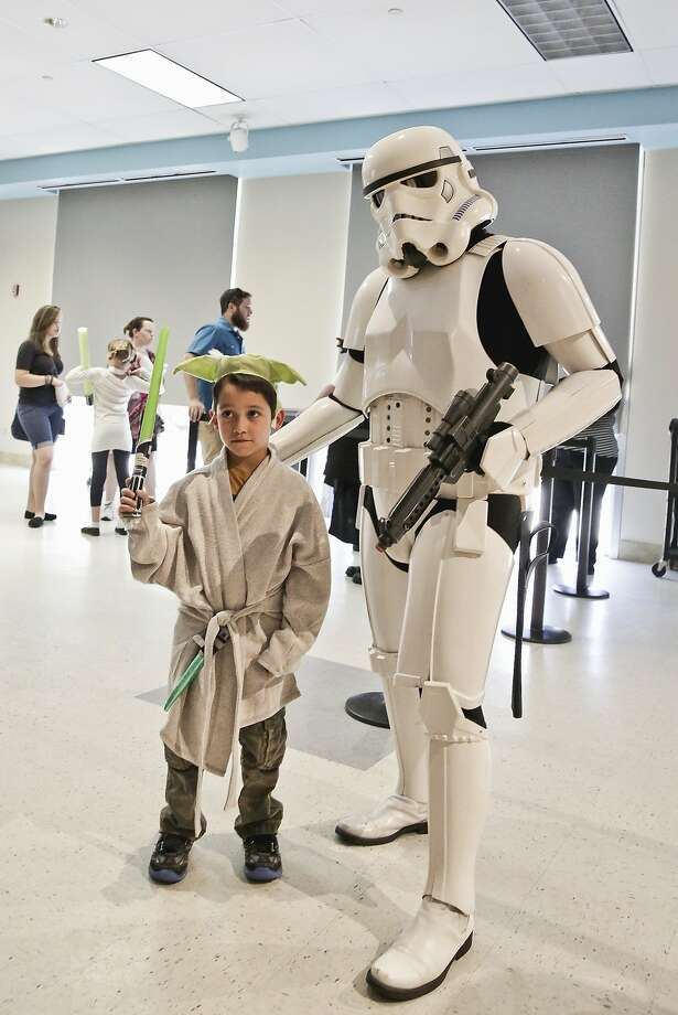 Manuel Barrera, left, poses for a photograph with a Stormtrooper cosplayer, Sunday afternoon, at the Laredo Public Library during the Star Wars Day: May the Fourth Be With You event. Photo: Victor Strife
