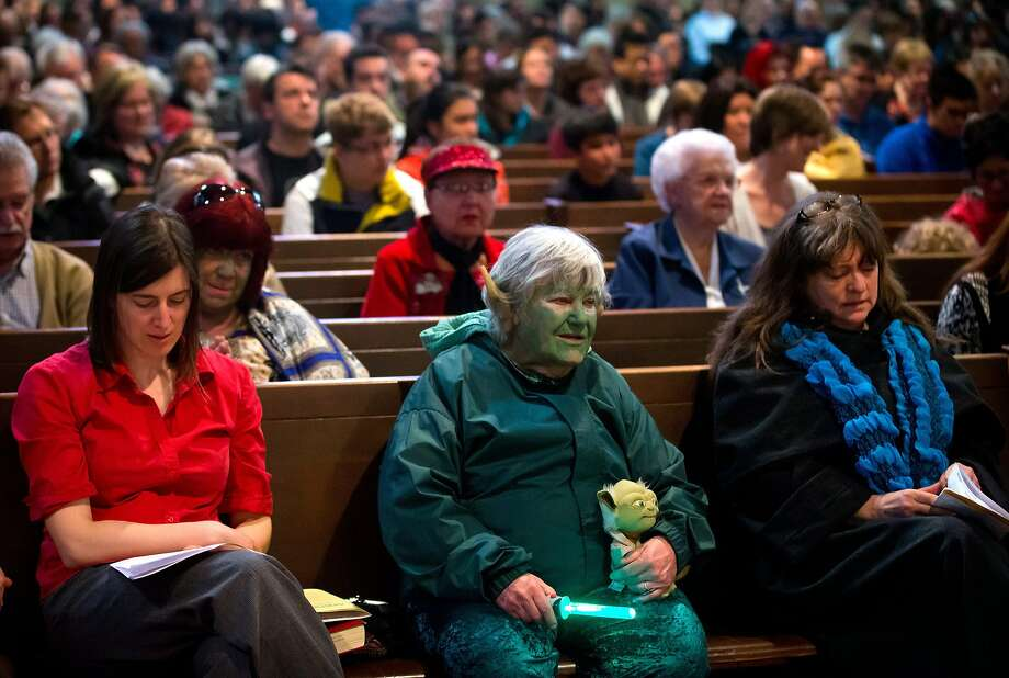 "Dressed as Yoda, Freeda Elliott, 78, center, listens during a Star Wars-themed church service at St. Andrew's-Wesley Church in Vancouver, British Columbia, Sunday, May 4, 2014. The service was held to mark Star Wars Day, May 4, chosen by fans because it sounds similar to the line from the series' phrase ""May the Force be with you,"" according to The Canadian Press. Photo: Darryl Dyck, Associated Press"