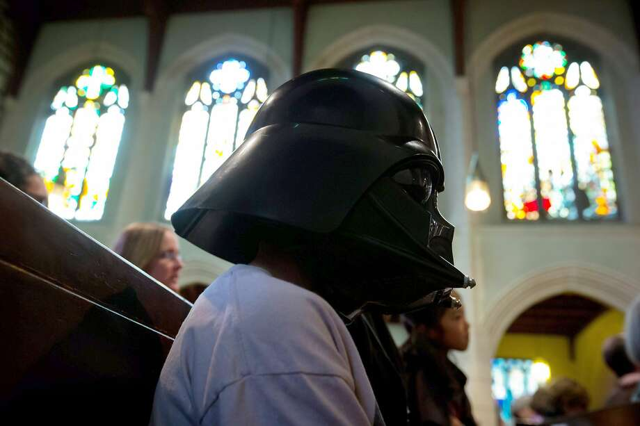 "Brandon Young wears a Darth Vader helmet while attending a Star Wars-themed church service with his family at St. Andrew's-Wesley Church in Vancouver, British Columbia, Sunday May 4, 2014. The service was held to mark Star Wars Day, May 4, chosen by fans because it sounds similar to the line from the series' phrase ""May the Force be with you,"" according to The Canadian Press. Photo: Darryl Dyck, Associated Press"