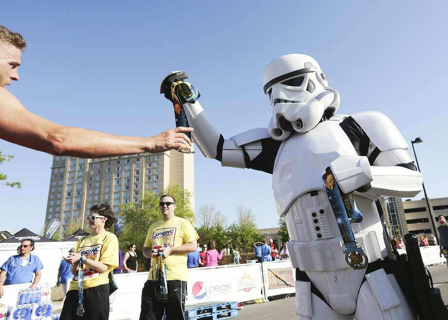 "A Star Wars storm trooper hands out medals to finishers of the Prairie Fire Marathon half marathon on Sunday, May 4, 2014, in Wichita, Kan. May 4 is known as National Star Wars Day to fans worldwide since the date is similar to the franchise's slogan, ""May the Force Be With You.""  Photo: Jaime Green, Associated Press"