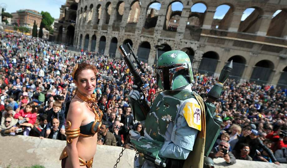 "A member of the Star Wars fan club dressed as Boba Fett (R) celebrates ""Star Wars Day"" in front of the Colosseum in central Rome on May 4, 2014. Photo: Tiziana Fabi, AFP/Getty Images"