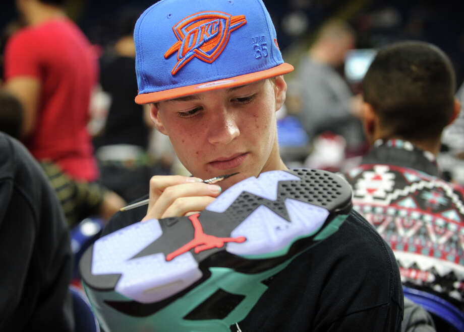 Sneaker customizer Matt Larned, 16, of Plainville, custom paints a pair of Nike Air Jordans at the inaugural Connecticut Sneaker Show at the Webster Bank Arena in Bridgeport, Conn. on Sunday, May 4, 2014. Photo: Brian A. Pounds / Connecticut Post