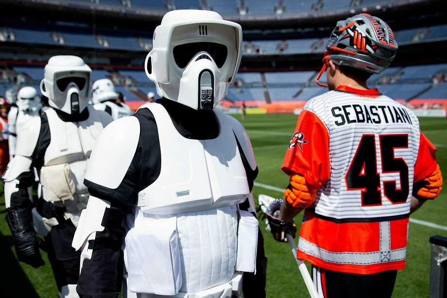 """Members of the Storm Troopers cross paths with Domenic Sebastiani #45 of the Denver Outlaws before a game against the Ohio Machine at Sports Authority Field at Mile High on May 4, 2014 in Denver, Colorado. The teams wore Star Wars themed jerseys in honor of """"May-The-4th-Be-With-You day."""" Photo: Justin Edmonds, Getty Images"""