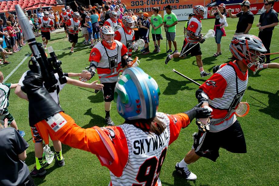 "The Denver Outlaws take the field as a member of the Rebel Alliance cheers them on before a game against the Ohio Machine at Sports Authority Field at Mile High on May 4, 2014 in Denver, Colorado. The teams wore Star Wars themed jerseys in honor of ""May-The-4th-Be-With-You day."" Photo: Justin Edmonds, Getty Images"