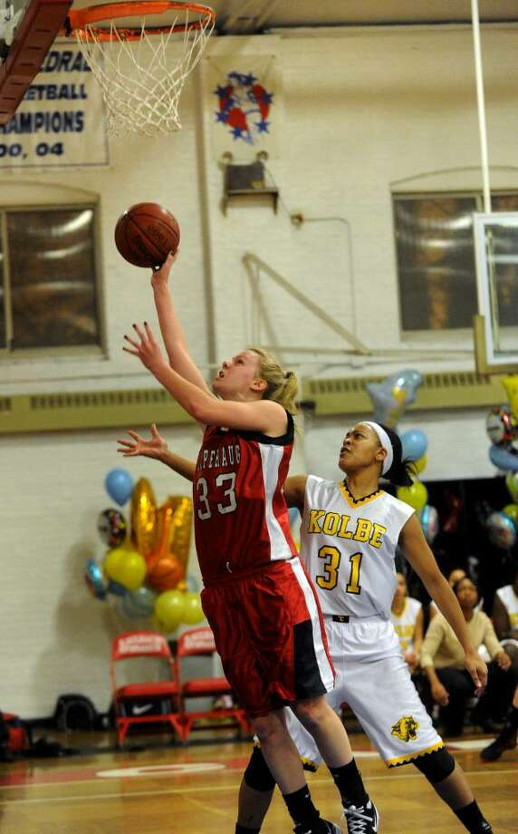 Pomperaug's #33 Kasey Dean looks for two points while Kolbe Cathedral's #31 Cherelle Moore looks to block, during basketball action in Bridgeport, Conn. on Friday Feb. 12, 2010. Photo: Christian Abraham / Connecticut Post