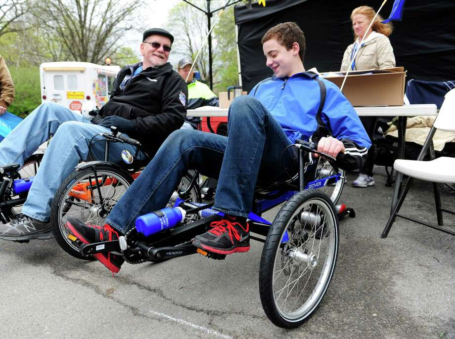 Bernie Elwood, left, shows Brandon Cosme, right, 14, of Albany, how to shift a TerraTrike bicycle, as Elwood's wife, Darlene Elwood, background, owner of Spikes Trikes in Amsterdam, works their booth at the Albany Bike Expo on Sunday, May 4, 2014, in Washington Park in Albany, N.Y.  The bike expo in its fourth year, brings together bike shops and riding groups along with booths on riding information for transportation alternatives.   (Paul Buckowski / Times Union) Photo: Paul Buckowski / 00026723A