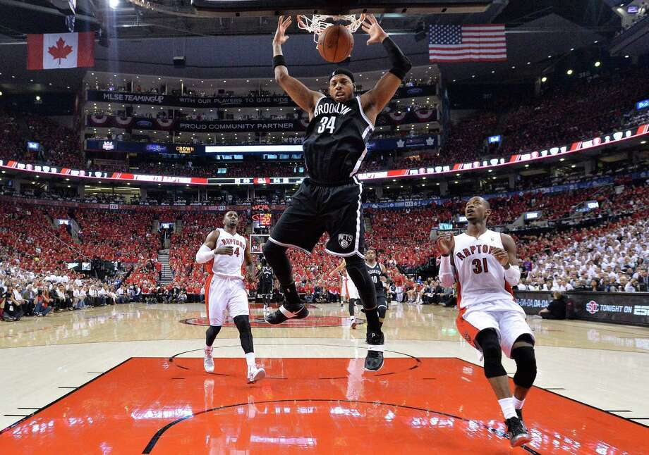 Brooklyn Nets forward Paul Pierce (34) dunks the ball past Toronto Raptors guard Terrence Ross (31) during first half NBA game seven playoff basketball action in Toronto on Sunday, May 4, 2014. (AP Photo/The Canadian Press, Nathan Denette) ORG XMIT: NSD122 Photo: Nathan Denette / CP