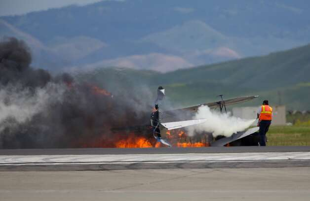 An emergency responder works to control a fire after a biplane crashed at an air show at Travis Air Force Base on May 4, 2014. Photo: Bryan Stokes, Special To The Chronicle
