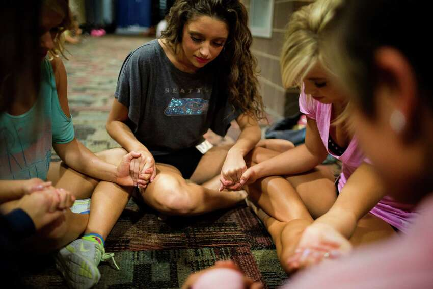 Sea Gal Christian, center, and other young women pray before the final auditions for the 2014 Sea Gals squad Sunday at CenturyLink Field in Seattle. Final auditions included individual and group performances, along with a kick line section.