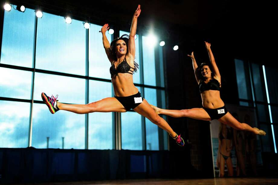 Natalie, left, and Kaylee, right, leap during their performance at the final audition for the 2014 Sea Gals squad Sunday at CenturyLink Field in Seattle Final auditions included individual and group performances, along with a kick line section. Photo: JORDAN STEAD, SEATTLEPI.COM / SEATTLEPI.COM