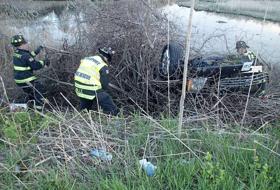 Westport firefighters extricate two people from a vehicle that overturned down on an embankment after a crash early Monday on Interstate 95 between southbound Exits 18 and 17. Photo: Westport Fire Department / Westport News