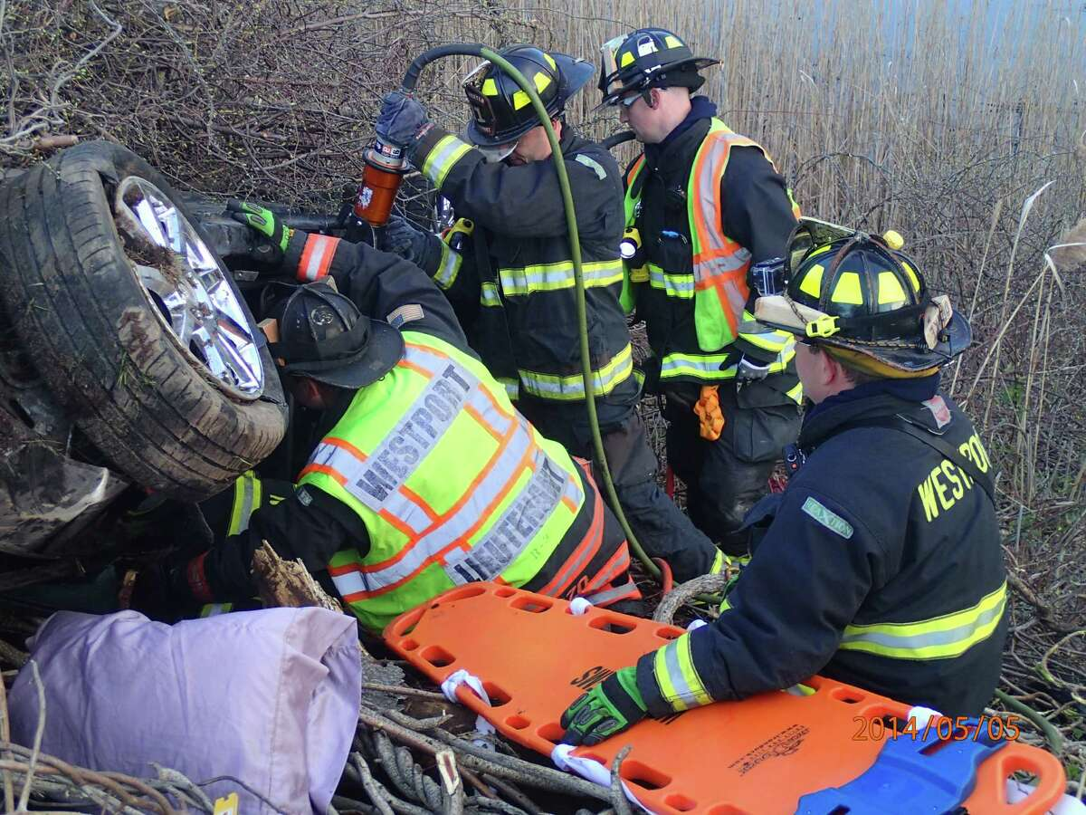 Westport firefighters extricate two people from a vehicle that overturned down on an embankment after a crash early Monday on Interstate 95 between southbound Exits 18 and 17.