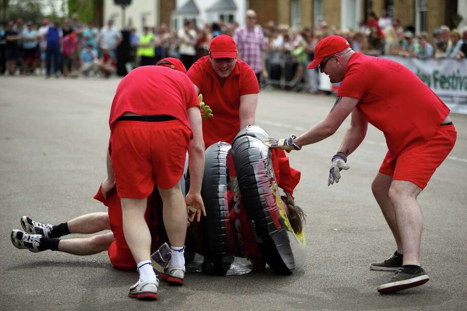 A team attempt to roll a wooden 'cheese' whilst dressed in inflatable rubber-rings during the Stilton Village Festival cheese rolling competition on May 5, 2014 in Stilton, England. The Stilton annual cheese rolling competition, which is held annually on every May Day Bank Holiday involves teams of four competing against each other by rolling cheese down the High Street to be crowned the 'Stilton Cheese Rolling Champions'. Photo: Jordan Mansfield, Getty Images / 2014 Getty Images