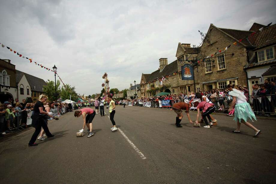 A general view of Stilton High Street as teams participate in the cheese rolling competition on May 5, 2014 in Stilton, England. The Stilton annual cheese rolling competition, which is held annually on every May Day Bank Holiday involves teams of four competing against each other by rolling cheese down the High Street to be crowned the 'Stilton Cheese Rolling Champions'. Photo: Jordan Mansfield, Getty Images / 2014 Getty Images