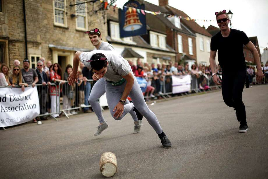 A team roll a wooden 'cheese' during the Stilton Village Festival cheese rolling competition on May 5, 2014 in Stilton, England. The Stilton annual cheese rolling competition, which is held annually on every May Day Bank Holiday involves teams of four competing against each other by rolling cheese down the High Street to be crowned the 'Stilton Cheese Rolling Champions'. Photo: Jordan Mansfield, Getty Images / 2014 Getty Images