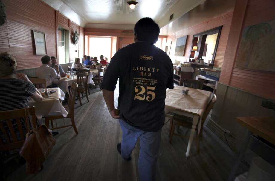 Oscar Trejo, manager of Liberty Bar, goes to greeted patrons as they enjoy their last lunch at the historic eatery before it moved to it's new location in Southtown. Photo: Bob Owen, Express-News