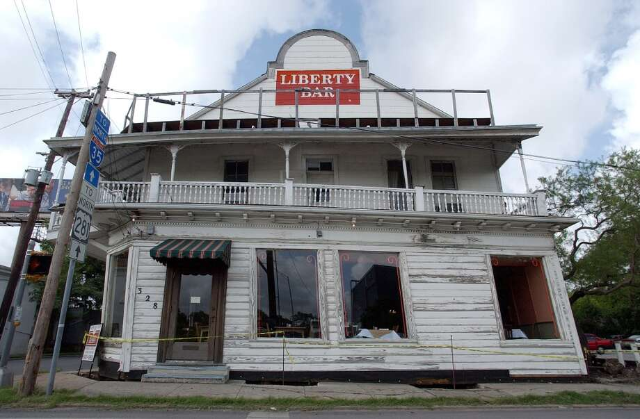 """The well-known Liberty Bar undergoes maintenance to shore up its foundation. The """"tilt"""" of the structure remains as its distinct feature in 2003. Photo: Kin Man Hui, Express-News"""