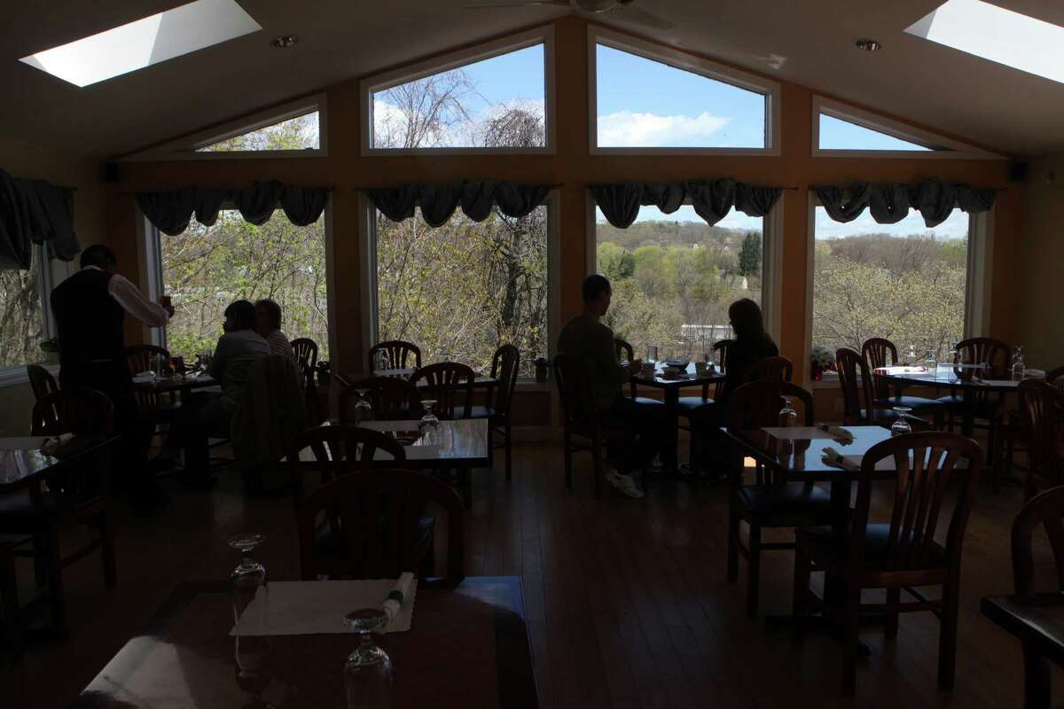 The main dinning room of Baingan Indian restaurant in Shelton, Conn. overlooks the Housatonic River. Sunday, May 4, 2014.