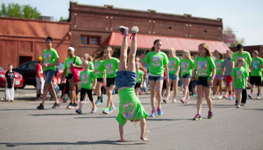 Show-off:An Apple Blossom Parade participant marches down Frederick Avenue in St. Joseph,   Mo., on her hands. Photo: Sait Serkan Gurbuz, Associated Press